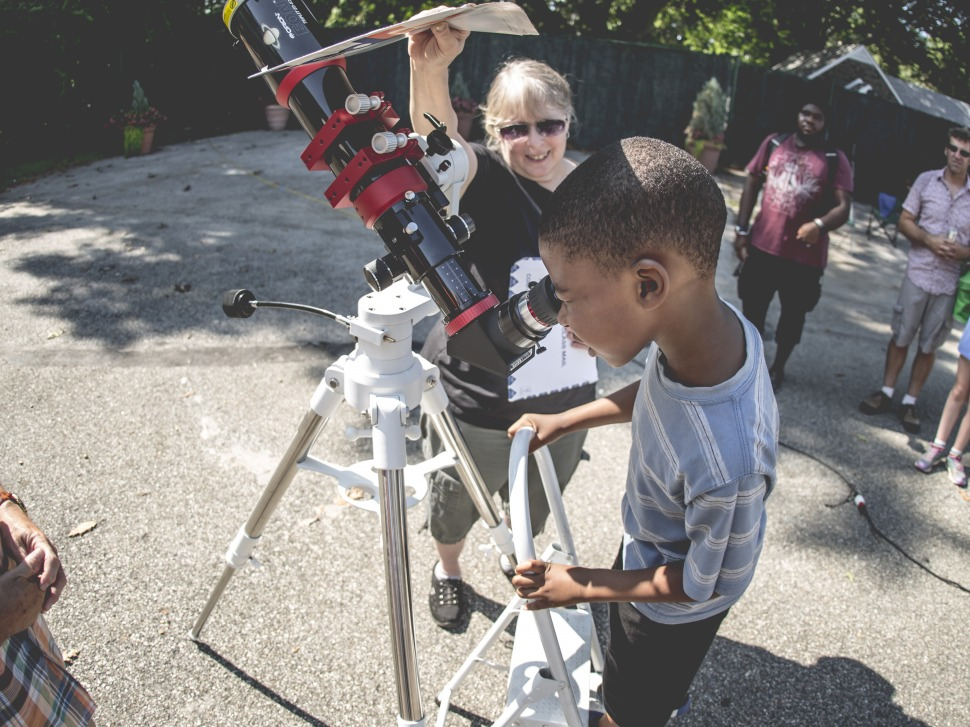 Child looking through a telescope